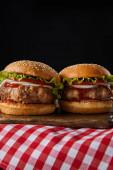 zwei Hamburger auf hölzernem Schneidebrett auf karierter Tischdecke isoliert auf schwarz