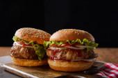 dva hamburgery na dřevěných řezacích deskách izolovaných na černé