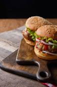 zwei Hamburger auf hölzernen Schneidebrettern isoliert auf schwarz
