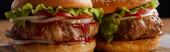 Panoramaaufnahme von zwei Hamburgern auf hölzerner Fläche isoliert auf schwarz