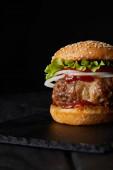 vynikající burger na tmavém dřevěném povrchu izolované na černé
