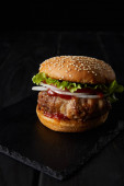 chutný burger na dřevěném povrchu izolované na černé