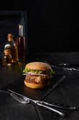 selektivní zaměření burgeru na tmavou sekací desku, vidličku, nůž, olejové a octové láhve izolované na černé