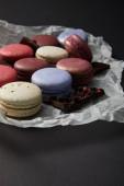 Nahaufnahme von verschiedenen köstlichen bunten französischen Makronen auf zerknülltem Papier mit Schokolade auf schwarzem Hintergrund