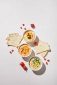 Fényképek Top kilátás tálak finom hummus, érett zöldségek és pitakenyér szürke alapon