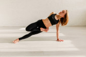 attractive woman doing side plank exercise in yoga studio