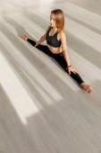 krásná žena dělá motouzy protahování na podlaze