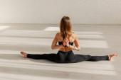 zpět pohled na ženu v obrácené modlitbě póza dělá motouzy protahování na podlaze