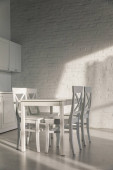 chairs and table near brick wall in modern kitchen