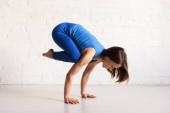 boční pohled na atletickou dívku v modrém sportovním oblečení dělá vrány póza