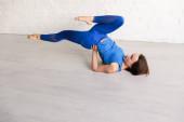 fiatal nő csinál kék sportruházat gyakorló jóga a padlón