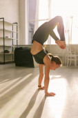 Photo sunlight near young woman with barefoot doing headstand exercise in yoga studio