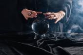 Oříznutý pohled na čarodějnice provádějící rituál s křišťálovou koulí na černém pozadí