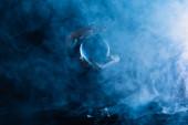 Oříznutý pohled na čarodějnice drží křišťálovou kouli na tmavomodrém pozadí