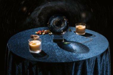 Mum ve servetin yanında kristal top koyu mavi kadife kumaş üzerinde taşlar söylüyor.