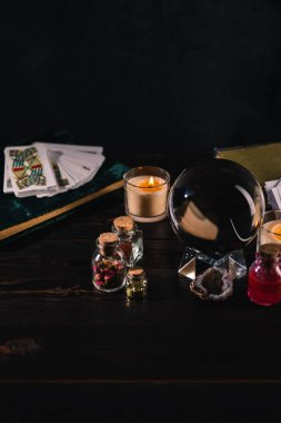KYIV, UKRAINE - JANUARY 9, 2020: tarot cards and crystal ball with occult objects on wooden and black background stock vector