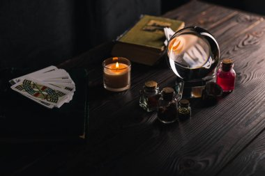 KYIV, UKRAINE - JANUARY 9, 2020: selective focus of crystal ball near occult and mystical objects on table on dark background stock vector