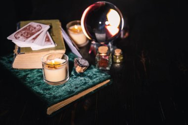 KYIV, UKRAINE - JANUARY 9, 2020: selective focus of crystal ball, books, candles, tarot cards and jars with dried herbs on dark background stock vector