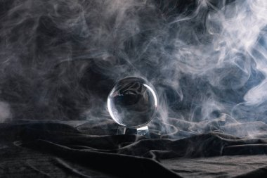 Crystal ball on black textile with smoke on dark background stock vector