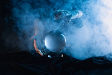 Cropped view of witch performing ritual with crystal ball on dark blue background