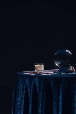 Kyiv, Ukrayna - 9 Ocak 2020: siyah masa üzerinde izole edilmiş mum ve okült cisimlerle kristal küre