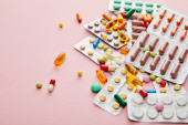 High angle view of colorful medicines on pink
