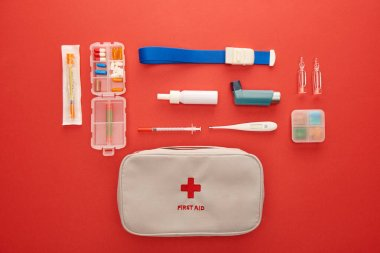 Flat lay with first aid kit, pills and medical objects on red background stock vector