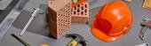 Panoramaaufnahme von Ziegeln, Hammer, Winkelschlüsseln, orangefarbenem Helm, Bremssätteln und Spachtelmesser auf grauem Hintergrund