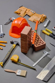 high angle view of bricks, industrial tools and helmet on grey background