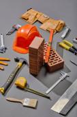Fotografie vysoký úhel pohledu cihel, průmyslových nástrojů a přilby na šedém pozadí