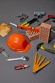 high angle view of tool belt, bricks, industrial tools and orange helmet on grey background