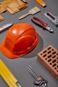 Fotografie flache Verlegung mit orangefarbenem Helm, Ziegel, Pinsel, Ziegel, Werkzeuggurt und Industriewerkzeugen auf grauem Hintergrund