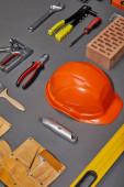 flat lay with orange helmet, tool belt, brick, industrial tools and brush on grey background