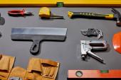 vysoký úhel pohledu na lihoviny, kleště, měřicí páska, kladivo, tmel nůž, úhlové klíče, sešívačka a pás na šedém pozadí