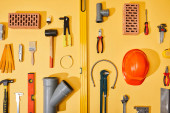 Photo flat lay with industrial tools, bricks and helmet on yellow background