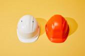 Ansicht von orangefarbenen und weißen Helmen auf gelbem Hintergrund