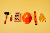flat lay with hammer, pliers, brick, helmet, spirit level and folding ruler on yellow background