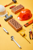 Fotografie Hochwinkelaufnahme von Ziegeln, Helmen und Industriewerkzeugen auf gelbem Hintergrund