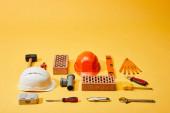 vysoký úhel pohledu na cihly, přilby a průmyslové nástroje na žlutém pozadí