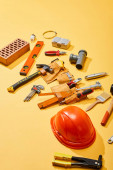 high angle view of tool belt, industrial tools, brick and helmet on yellow background