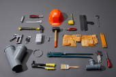 Photo flat lay with industrial tools, helmet, and tool belt on grey background