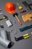 flat lay with helmet, tool belt and industrial tools on grey background