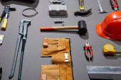 Photo high angle view of tool belt, helmet, hammers, monkey wrench, putty knife, pliers, calipers, rivet gun and measuring tape on grey background
