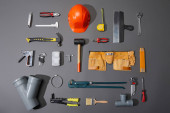 Photo flat lay of industrial tools, helmet, measuring tape, tool belt and brush on grey background