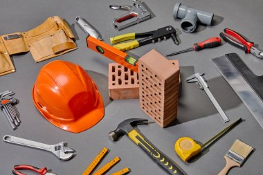 High angle view of industrial tools, bricks and helmet on grey background stock vector