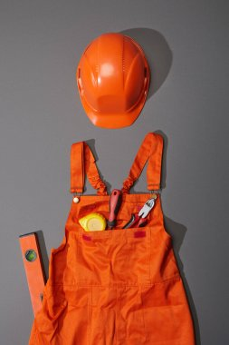 Top view of orange helmet and overalls with measuring tape, screwdriver and pliers near spirit level on grey background stock vector