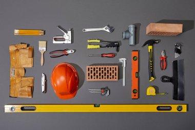 Flat lay with bricks, orange helmet, tool belt and industrial tools on grey background stock vector