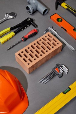 Flat lay with orange helmet, brick, rivet gun, hammer, screwdriver, calipers, spirit level, angle keys and pipe connector on grey background stock vector