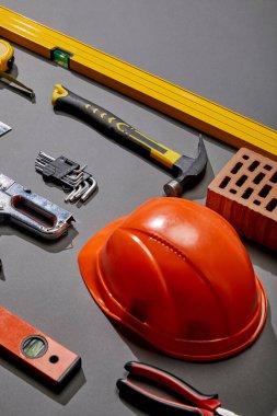 High angle view of orange helmet, hammer, spirit levels, brick, angle keys, pliers, stapler and measuring tape on grey background stock vector