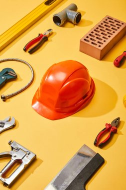 flat lay with industrial tools, helmet and brick, on yellow background